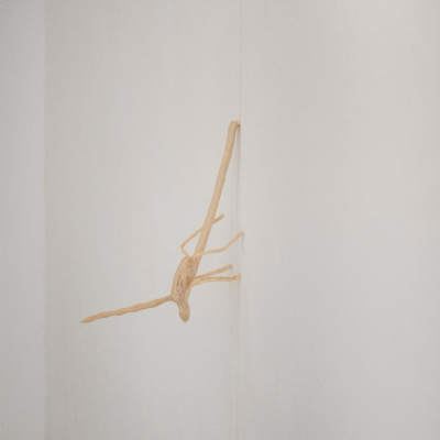 """Zuza Piekoszewska, """"Future Traveler"""", 2020, courtesy of the artist: Vertical shot of the object placed on a white wall. Beige, slender silhouettewith two clearly longer and thicker ramifications and four thinner and shorter legs."""