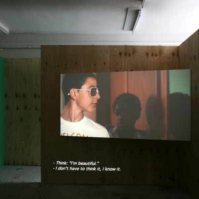 """Wendelien van Oldenborgh, """"Après la reprise, la prise"""", 2009, analogue slide projection with soundtrack, architectural setting, 15 min, Wilfried Lentz (Rotterdam), photograph by Bárbara Wagner, courtesy of the artist. : The film by Wendelien van Oldenborgh is being shown on the wall. A young white man is talking to someone, a black boy is standing behind him."""