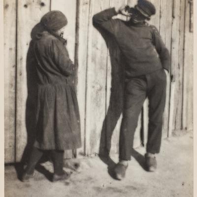 """JulianMioduszewski,""""Przy parkanie"""", 1928 r., fotografia czarno-biała, brom, z kolekcji Muzeum Sztuki w Łodzi : Fotografia czarno-biała przedstawiająca kobietę i mężczyznę prowadzących dialog w anturażu wiejskiego otoczenia."""