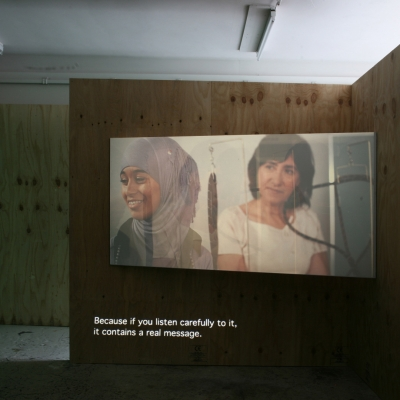 """Wendelien van Oldenborgh, """"Après la reprise, la prise"""", 2009, analogue slide projection with soundtrack, architectural setting, 15 min, Wilfried Lentz (Rotterdam), photograph by Bárbara Wagner, courtesy of the artist. : The film by Wendelien van Oldenborgh is being shown on the wall. Two women are talking to each other. One of them is middle-aged with longer brown hair; the other is younger and wears a gray hijab."""