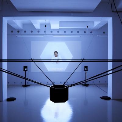 """András Cséfalvay, """"Szczyt bogów"""", 2019, wideo, fot.: Miklós Surányi, dzięki uprzejmości artysty: Poziome ujęcie instalacji w zaciemnionym zimno-białym wnętrzu. Na pierwszym planie zawieszona na suficie ciemna instalacja z sześciokątnym cylindrem w centrum  i odchodzącymi od niego na boki w górę rurkami. W tle obraz z rzutnika z siedzącą postacią w białym sześciokącie."""