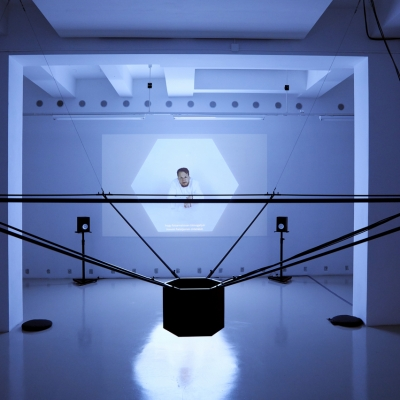 """András Cséfalvay, """"Summit of Gods"""", 2019, video, photo by Miklós Surányi, courtesy of the artist: Horizontal view of the installationin a darkened, cold-white interior. In the foreground, a dark installation suspended from the ceiling with a hexagonal cylinder in the centerand pipes extending from it to the sides. In the background a picturefrom a projector with a seated figurein a white hexagon."""