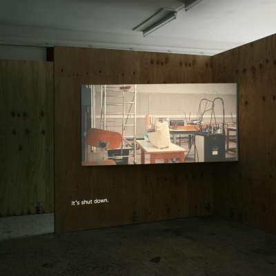 """Wendelien van Oldenborgh, """"Après la reprise, la prise"""", 2009, analogue slide projection with soundtrack, architectural setting, 15 min, Wilfried Lentz (Rotterdam), photograph by Bárbara Wagner, courtesy of the artist. : The film by Wendelien van Oldenborgh is being shown on the wall. The studio is empty. There are desks, equipment and a ladder with a broom. It gives the impression of being abandoned."""