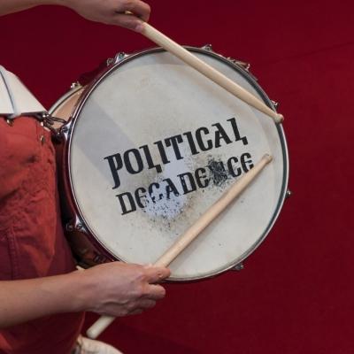 """Jasmina Cibic, """"Cała ta moc roztapia się w zgiełku"""", widok wystawy, Museum of Contemporary Art Metelkova, fot: Matevž Paternoster, dzięki uprzejmości artystki: Fotografia przedstawia biały werbel z napisem """"Political decadence"""", zdjęcie wykonane jest z góry. Osoba ubrana w czerwony kombinezon trzyma werbel i pałki perkusyjne, tło również jest czerwone."""
