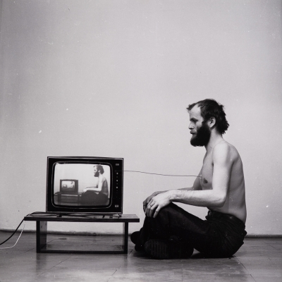 """Paweł Kwiek, """"Video and breath. The channel of information"""", 1978/2016, black-and-white photograph, from the collection of Muzeum Sztuki in Łódź: A black-and-white photograph shows a man facing the TV. The photograph documents a performance in which the artist coupled his breath with the TV screen."""