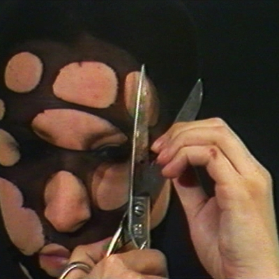 """Sanja Iveković, """"Personal cuts"""", 1982, colour film with sound (analogue recording transfered to digital), 3'43"""", collection of Muzeum Sztuki, Łódź: A woman is cutting with scissors a black piece of material which is on her head."""