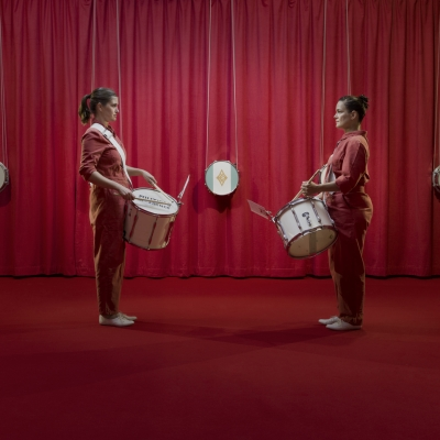 """Jasmina Cibic, """"All that power melts into noise"""", exhibition view, Museum of Contemporary Art Metelkova, photo: Matevž Paternoster, courtesy of the artist: Two women wearing red overalls are facing each other. They have white drums, they are looking at each other. In the background, there is a red curtain and smaller snare drums are hung on it. The floor is covered with red carpeting."""