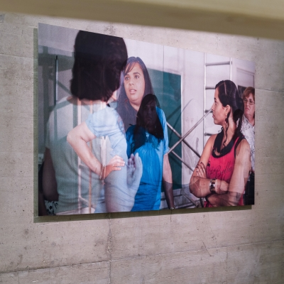 """Wendelien van Oldenborgh, """"Footnote to Après la reprise, la prise"""", 2016, lenticular print, installation view, Kunsthalle (Wien), photograph by  Kunst-Documentation.com, courtesy of the artist.: Three young, presumably Latino, women are talking to each other."""