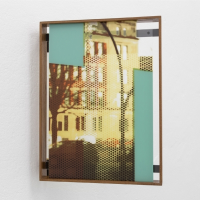 """Céline Condorelli, """"Afterimage 4 & How Things Appear, after Carlo Scarpa (frame)"""", 2016, installation view, Kunsthalle (Lisbon), photograph by Bruno Lopes, courtesy of the artist.: A composition enigmatically shows the city landscape covered with geometric shapes situated diagonally. The dominant colors are shades of brown, yellow and turquoise. The artwork is framed by a minimalist wooden frame that closes the composition. It was done using the serigraphy technique on an acrylic base."""