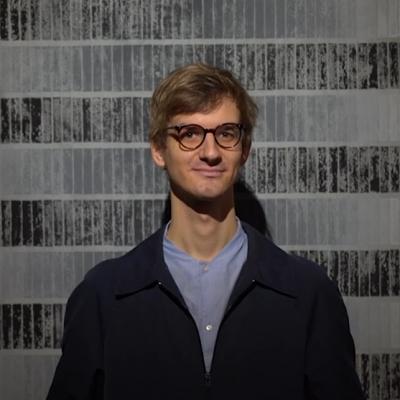 Kurator Jakub Gawkowski na tle wystawy, kadr z produkcji wideo Muzeum Sztuki w Łodzi i HaWy