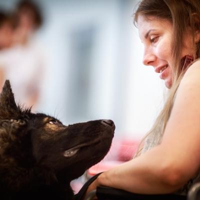 fot. T. Ogrodowczyk: Fotografia prezentuje uczestniczkę wydarzenia, która siedzi i spogląda na psa. Zwierzę także patrzy na kobietę.