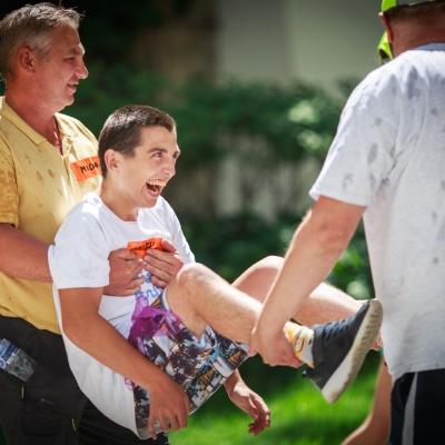 fot. T. Ogrodowczyk: Uczestnicy i uczestniczki wydarzenia (trzy osoby) w ogrodzie ms¹. Dwóch mężczyzn niesie uśmiechniętego chłopaka.
