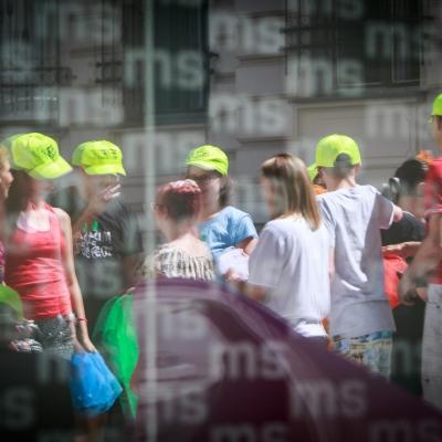 fot. T. Ogrodowczyk: Uczestnicy i uczestniczki wydarzenia (wiele osób) na dziedzińcu ms¹. Na pierwszym planie szklana szyba z logotypem Muzeum Sztuki w Łodzi (ms).