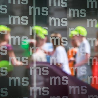 fot. T. Ogrodowczyk: Uczestnicy i uczestniczki wydarzenia (wiele osób) na dziedzińcu ms¹ (ich postaci są niewyraźne). Na pierwszym planie szklana szyba z logotypem Muzeum Sztuki w Łodzi (ms).