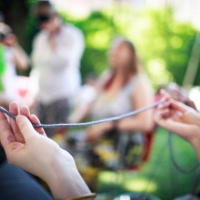 fot. T. Ogrodowczyk: Uczestnicy i uczestniczki wydarzenia (wiele osób) w ogrodzie ms¹ (ich postaci znajdują się w tle, są niewyraźne). Na pierwszym planie widać dłonie trzymające szary sznurek.