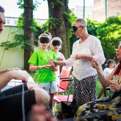 fot. T. Ogrodowczyk: Uczestniczki wydarzenia (wiele osób) w ogrodzie ms¹. Na pierwszym kierownik Działu Edukacji Leszek Karczewski oraz siedząca kobieta, nieco dalej - dwie stojące dziewczynki i kobieta (wszystkie z czarnymi opaskami na oczach).