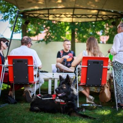 fot. T. Ogrodowczyk: Uczestnicy i uczestniczki wydarzenia (wiele osób) w ogrodzie ms¹. Na scenie siedzi kierownik Działu Edukacji Leszek Karczewski. Przed nim siedzi kilka osób, jedna kobieta stoi. Na pierwszym planie, w centrum zdjęcia widać leżącego psa-przewodnika.