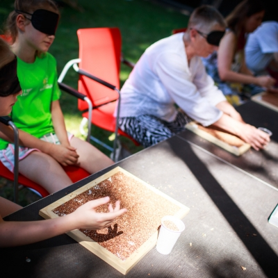fot. T. Ogrodowczyk: Uczestnicy i uczestniczki wydarzenia (wiele osób) w ogrodzie ms¹. Wszyscy siedzą. Na scenie przed nimi leży sypki materiał w surowej, drewnianej ramce. Niektórzy go dotykają.