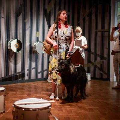 """fot. T. Ogrodowczyk: Publiczność (wiele osób) w przestrzeni wystawy """"Jasmina Cibic. Pałac"""". Osoba na pierwszym planie (kobieta wraz z psem-przewodnikiem) stoi, na dalszym planie znajdują się edukatorka Katarzyna Mądrzycka-Adamczyk oraz inni uczestnicy wydarzenia."""