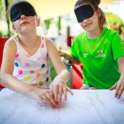 fot. T. Ogrodowczyk: Uczestniczki wydarzenia (dwie dziewczynki w czarnych opaskach na oczach) w ogrodzie ms¹. Przed nimi leży biały papier z substancją przypominającą klej.