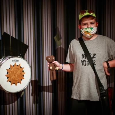 """fot. T. Ogrodowczyk: Fotografia prezentuje chłopaka w żółtej czapce z daszkiem, który trzyma w prawej ręce pluszowego misia. Znajduje się w sali ekspozycyjnej. Po lewej stronie werbel pochodzący z wystawy """"Jasmina Cibic. Pałac""""."""