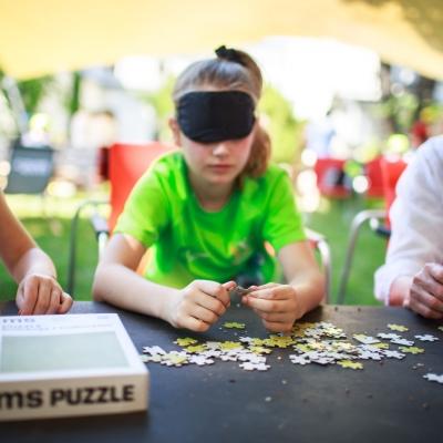 """fot. T. Ogrodowczyk: Uczestniczki wydarzenia (dwie dziewczynki i kobieta w czarnych opaskach na oczach) w ogrodzie ms¹. Przed nimi leżą puzzle i pudełko z napisem """"ms puzzle""""."""