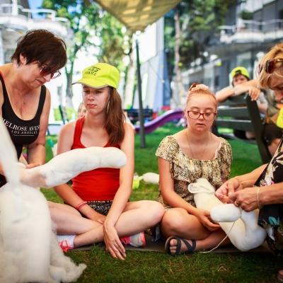 fot. T. Ogrodowczyk: Na pierwszym planie znajdują się uczestniczki wydarzenia (dwie dziewczynki i dwie kobiety) w ogrodzie ms¹. Siedzą. W tle - inna uczestniczka, która siedzi na drewnianej, ciemnej ławce.