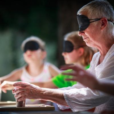 fot. T. Ogrodowczyk: Uczestniczki wydarzenia (dwie dziewczynki i kobieta w czarnych opaskach na oczach) w ogrodzie ms¹. Siedzą. Przed nimi stoją plastikowe kubki wypełnione różnymi materiałami.