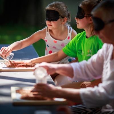 fot. T. Ogrodowczyk: Uczestniczki wydarzenia (dwie dziewczynki i kobieta w czarnych opaskach na oczach) w ogrodzie ms¹. Siedzą. Przed nimi stoją plastikowe kubki wypełnione różnymi materiałami. Dziewczynka wysypuje brązowy, sypki materiał z kubka.