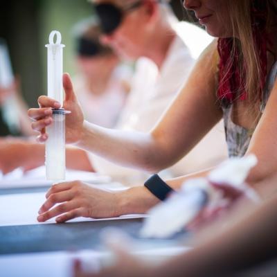 fot. T. Ogrodowczyk: Uczestniczki wydarzenia w ogrodzie ms¹. Siedzą. Kobieta trzyma w rękach strzykawkę z substancją, która wylewa się na biały papier.