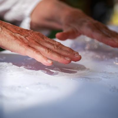 fot. T. Ogrodowczyk: Na zdjęciu widać dłonie osoby dorosłej, które unoszą się nad białym papierem. Na nim znajduje się zaś substancja przypominająca klej.