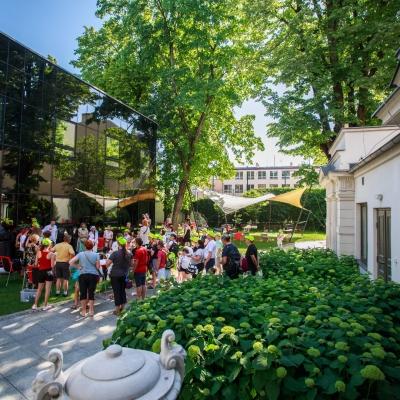 fot. T. Ogrodowczyk: Uczestnicy i uczestniczki wydarzenia (wiele osób) w ogrodzie ms¹. Niektórzy siedzą na ławkach, inni stoją. Ujęcie z oddali.