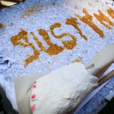 """fot. T. Ogrodowczyk: Na tekturze leży papier czerpany z brokatowym napisem """"Justyna"""""""