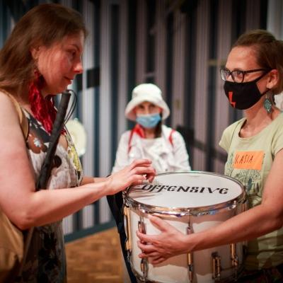 fot. T. Ogrodowczyk: Po prawej stronie edukatorka Katarzyna Mądrzycka-Adamczyk, trzymająca werbel pochodzący z wystawy prac Jasminy Cibic. Po lewej stronie uczestniczka wydarzenia. W tyle inni uczestnicy.