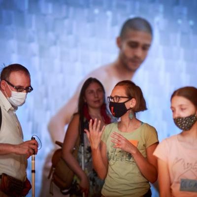fot. T. Ogrodowczyk: Publiczność (cztery osoby) w sali ekspozycyjnej. W tle projekcja filmowa.