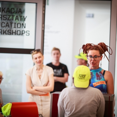 fot. T. Ogrodowczyk:  Fotografia prezentuje edukatorów oraz uczestników wydarzenia. W centrum zdjęcia znajduje się edukatorka Agnieszka Wojciechowska-Sej, która rozmawia z osobą w żółtej czapce z daszkiem.