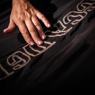 """fot. T. Ogrodowczyk: Fotografia prezentuje zbliżenie fragmentu tkaniny znajdującej się na wystawie """"Jasmina Cibic. Pałac"""". Kadr ukazuje również sensoryczny wydźwięk wystawy."""