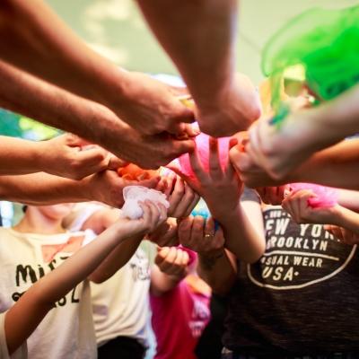 fot. T. Ogrodowczyk: Uczestnicy i uczestniczki wydarzenia (wiele osób) w ogrodzie ms¹. Wszyscy stoją i wyciągają do przodu ręce, w których trzymają zwinięte, kolorowe apaszki.
