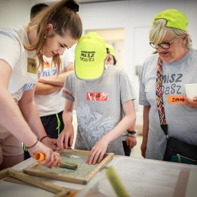 fot. T. Ogrodowczyk: Uczestnicy i uczestniczki wydarzenia (wiele osób) w sali warsztatowej ms¹. Na pierwszym planie dziewczyna i dwie osoby w żółtych czapkach z daszkiem.
