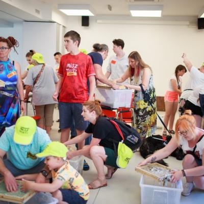 fot. T. Ogrodowczyk: Uczestnicy i uczestniczki wydarzenia (wiele osób) w sali warsztatowej ms¹. Na pierwszym planie osoby przysiadają na zgiętych kolanach, a na drugim - stoją.