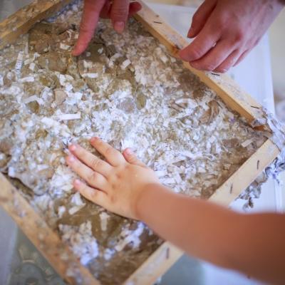 fot. T. Ogrodowczyk: Zbliżenie na dłonie osoby dorosłej i rękę dziecka. Dotykają pracy oprawionej w drewnianą, surową ramkę.