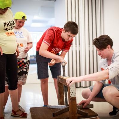 fot. T. Ogrodowczyk: Uczestnicy i uczestniczki wydarzenia (wiele osób) w sali warsztatowej ms¹. Na pierwszym planie mężczyzna przysiada na zgiętych kolanach, na drugim - ludzie stoją.