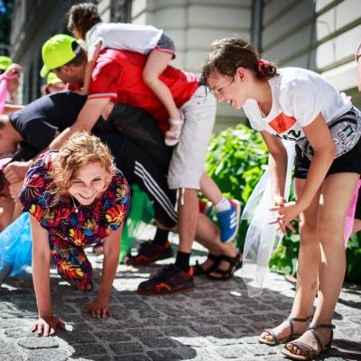 fot. T. Ogrodowczyk: Uczestnicy i uczestniczki wydarzenia (wiele osób) w ogrodzie ms¹. Na pierwszym planie widać uśmiechniętą edukatorkę Maję Pawlikowską oraz pochylającą się w jej kierunku uśmiechniętą dziewczynę.