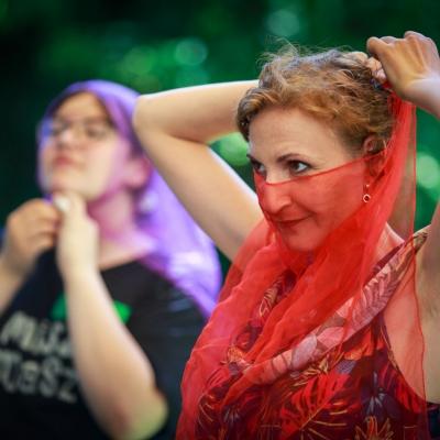 fot. T. Ogrodowczyk: Fotografia prezentuje edukatorkę Maję Pawlikowską. Ma twarz zakrytą półprzezroczystą, czerwoną apaszką. W tle - uczestniczka/uczestnik wydarzenia.