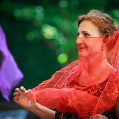 fot. T. Ogrodowczyk: Fotografia prezentuje edukatorkę Maję Pawlikowską, która zakrywa twarz półprzezroczystą, czerwoną apaszką. W tle - kobieta, uczestniczka wydarzenia.