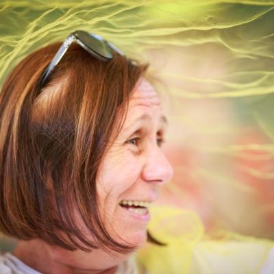 fot. T. Ogrodowczyk: Fotografia prezentuje uśmiechniętą uczestniczkę wydarzenia. Za nią widać półprzezroczystą, żółtą apaszkę.