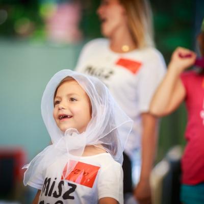 fot. T. Ogrodowczyk: Fotografia prezentuje uczestników i uczestniczki wydarzenia. Na pierwszym planie dziewczynka, która ma na głowie półprzezroczystą, białą apaszkę. Wszyscy stoją.