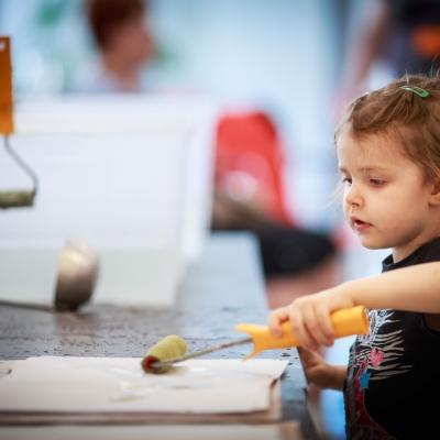 fot. T. Ogrodowczyk: Fotografia prezentuje uczestniczkę wydarzenia - kilkuletnią dziewczynkę, trzymającą w lewej ręce mały wałek malarski.