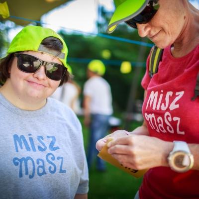 fot. T. Ogrodowczyk: Uśmiechnięta dziewczyna w przeciwsłonecznych okularach patrzy w obiektyw. Obok niej stoi osoba w czerwonej koszulce. Na głowach mają żółte czapki z daszkiem.