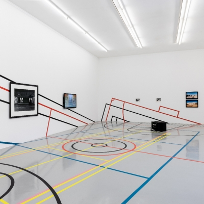 """Céline Condorelli, """"Limits to Play"""", 2020, installation view, FRAC Lorraine (France), photograph by Fred Dott, courtesy of the artist.: The photo shows the view of the exhibition. In the central part of the exhibition, there is an area that resembles a football field. The space has been divided by lines into zones in the colors of black, red, blue and yellow. There are photographs and video screens on the white walls, lined with colorful borders."""